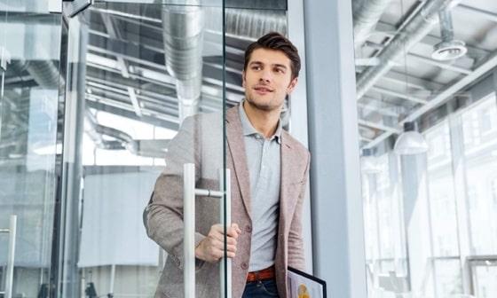 Man with clipboard entering the door in office